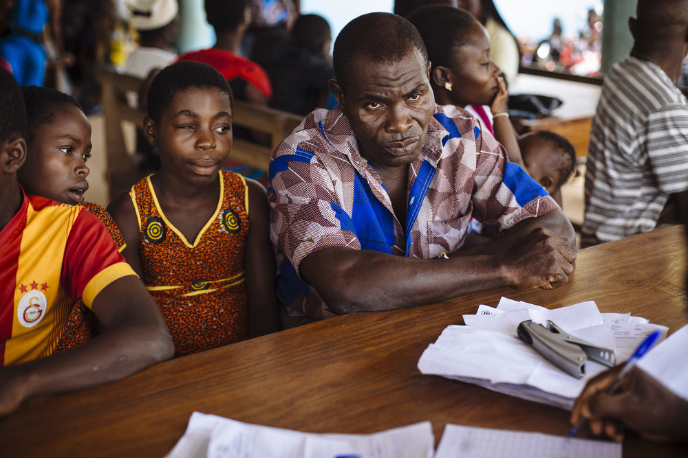 Gbohoun Hie, front right, listens to information provided by ASAPSU (Association de Soutien à l'Autopromotion Sanitaire et Urbaine) along with his daughters Hawae Hie, second from left, and Tahadi Hie, left, at the UNHCR Voluntary Repatriation Transit Center, Tabou, Bas-Sassandra District, Côte d'Ivoire.