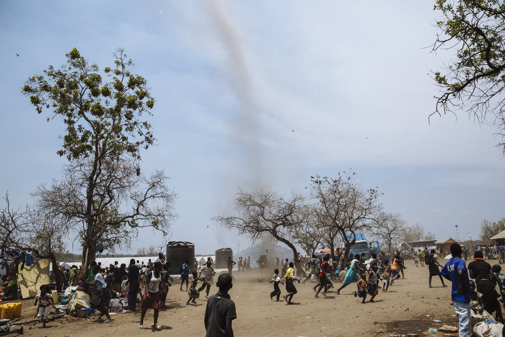South Sudanese refugees run away from a dust devil passing through the Imvepi Reception Centre, Arua District, Northern Region, Uganda.
