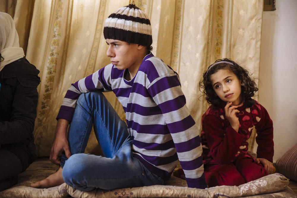 Syrian refugee Oday, 15, and his sister Diyala, 7, sit in the family's rented apartment in Madaba, Madaba Governorate, Jordan.