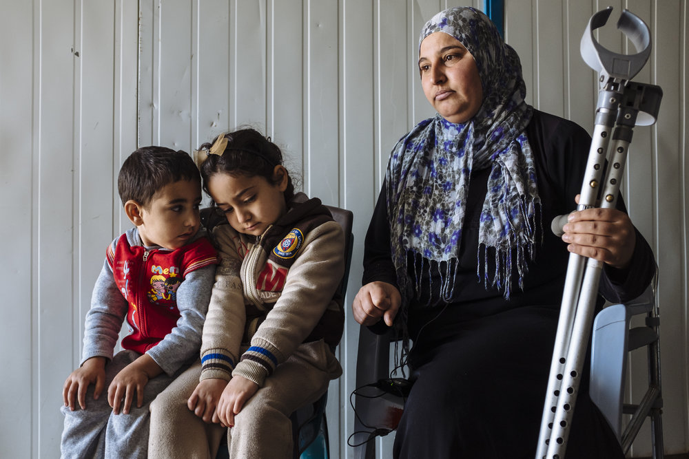 Syrian refugee Hoyada, right, who had her right leg amputated in 2014 after being diagnosed with osteosarcoma (bone cancer), her daughter Bisal, centre, and son Kenan, sit for an interview at their shelter in Za'atari refugee camp, Mafraq Governorate, Jordan.