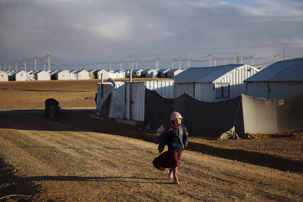 A young Syrian refugee makes her way down a road in Azraq refugee camp, Zarqa Governorate, Jordan.
