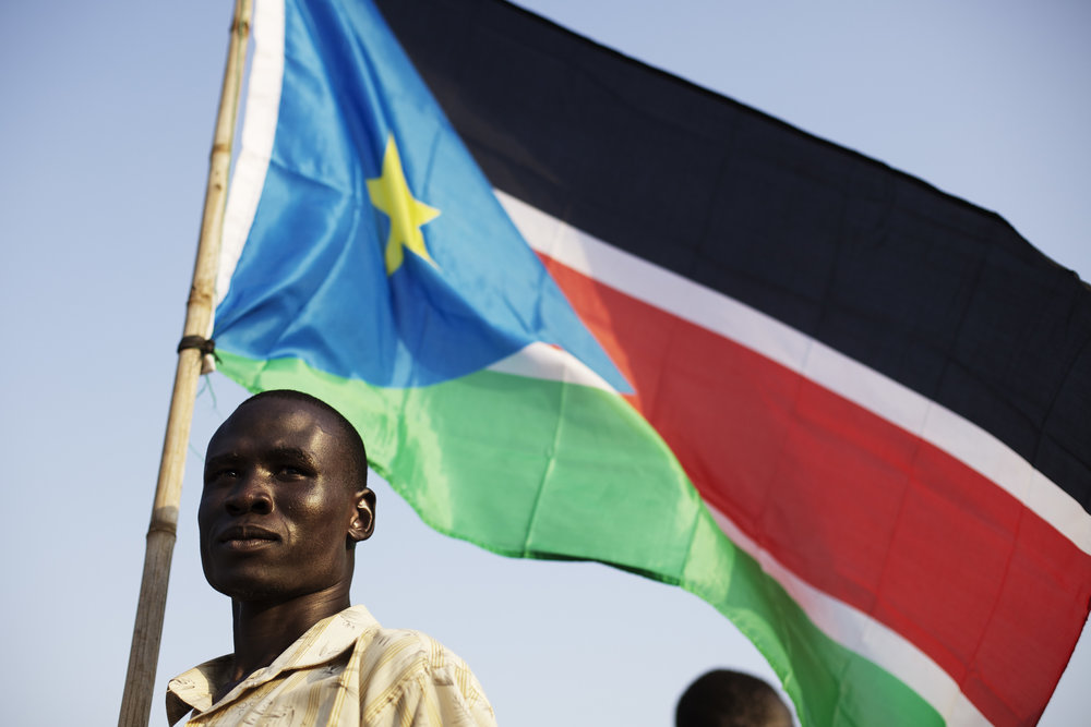 A Bari community member holds the flag of South Sudan during celebrations on the eve of South Sudan's declaration of independence in Juba, southern Sudan, Friday, July 8, 2011. (AP Photo/David Azia)