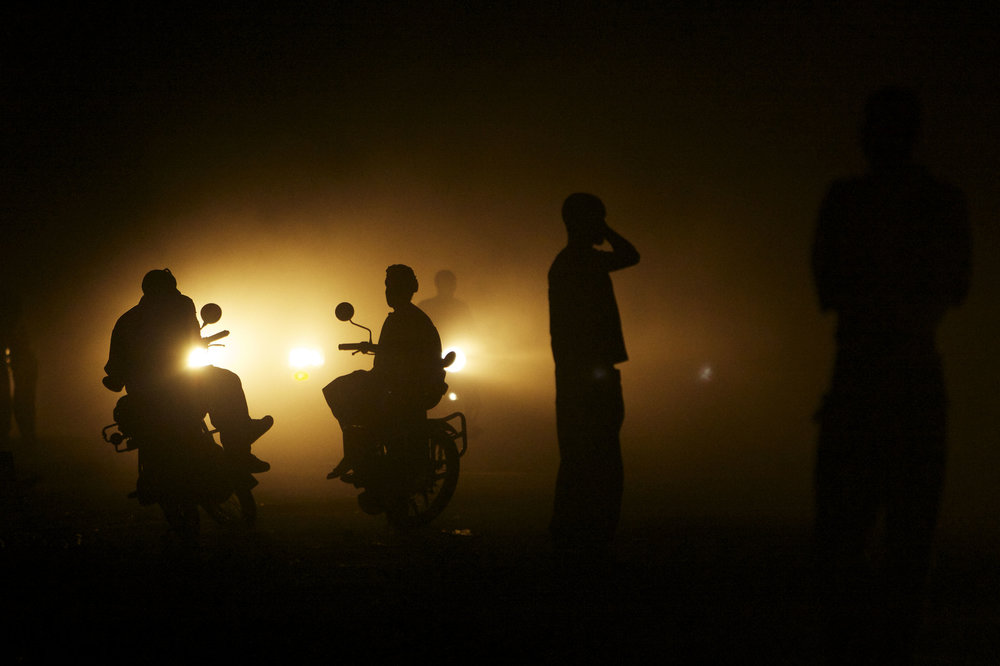 Pedestrians and motorcycle taxi drivers are silhouetted by oncoming traffic in Juba, South Sudan, Monday, July 11, 2011. (AP Photo/David Azia)