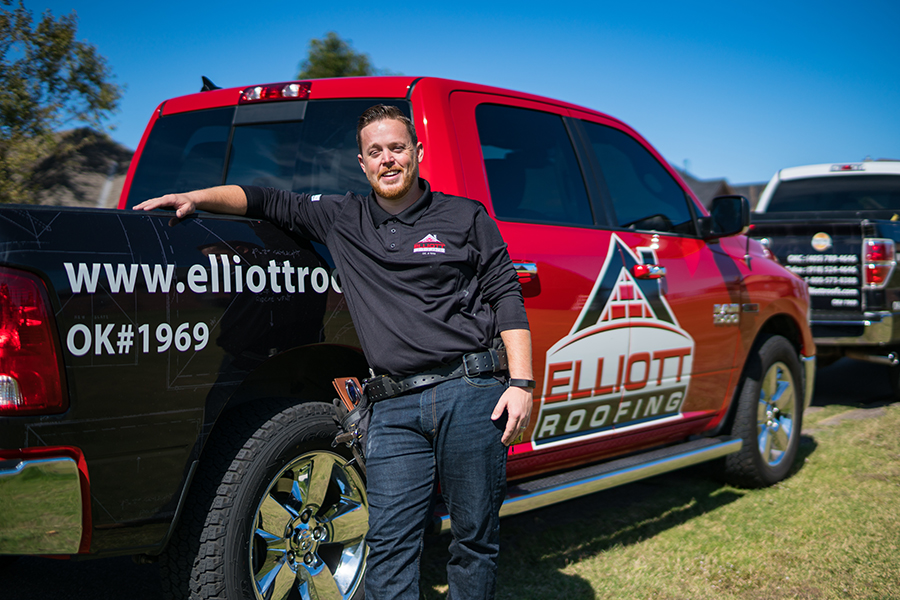 Elliott Roofing employee standing outside by his truck