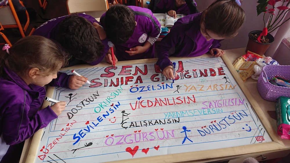 Children writing classroom codes of conduct for greeting their refugee friends…