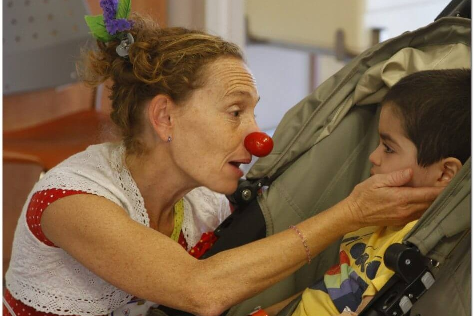 A Dream Doctor medical clown comforting a patient.