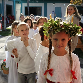 "Santa Lucia - A second grade student, dressed in white as Santa Lucia and wearing a golden crown aglow with four candles, leads a procession of classmates. Each holds a lit candle as they sing ""Santa Lucia"" and carry their light throughout the school. The second graders are busy for days before, baking saffron buns to share with their schoolmates, as the procession travels to all the other classes, including the Nursery/Kindergartens."