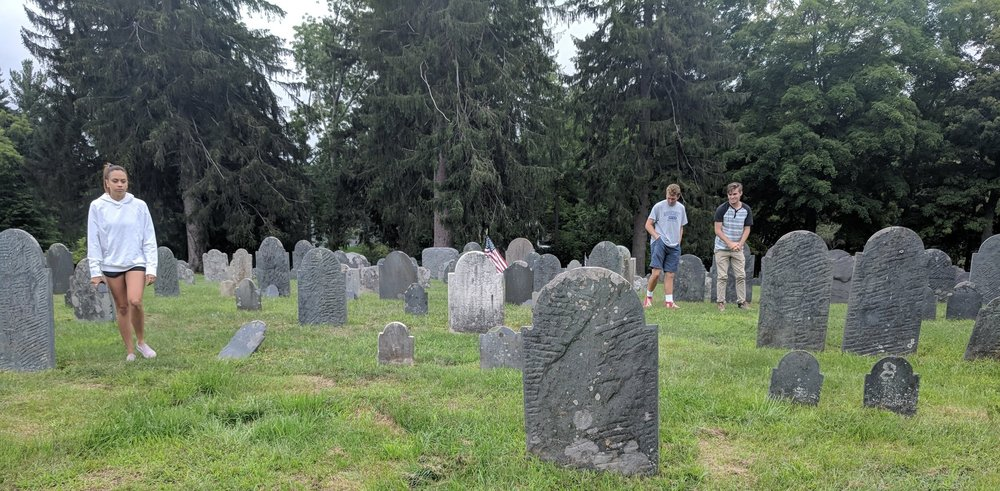 Taylor Galusha, Daniel Proulx, and Robert Tolan wander among the headstones.