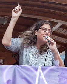 Image: Susan Stryker a white trans woman with long brown wavy hair and glasses speaking into a microphone and holding her finger in the air as she speaks to the audience.