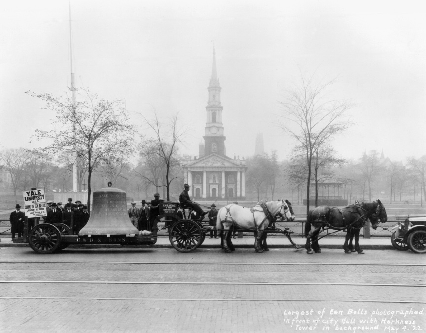 The bass bell of what became the Yale Memorial Carillon, on its way in 1922 past the New Haven Green. In the immediate background is Center Church on the Green, a Congregationalist parish established in 1639. The bell's Yale destination, Harkness Tower, is visible in the background fog. This bell was cast by John Taylor & Co., in Loughborough, England. It is pitched at concert F-sharp and weighs 13,400 pounds. Credit: Yale University.