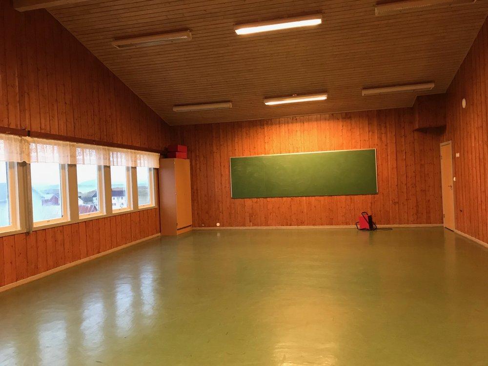 Stor tavle i motsatt ende av ribbeveggen. Storkjøkken vegg i vegg.  Vi disponerer 15 sammenleggbare bord og 100 stoler.