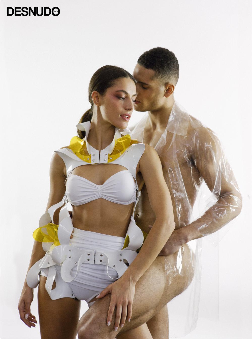 Desirée wears beachwear  NORMA KAMALI , harness  LEATHER ARTEFACT , shoes  MANOLO BLAHNIK , Danny wears shirt  NORMA KAMALI