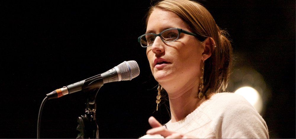 Image: A head shot of Liz speaking into a microphone, wearing a white sweater and long gold dangly earrings.