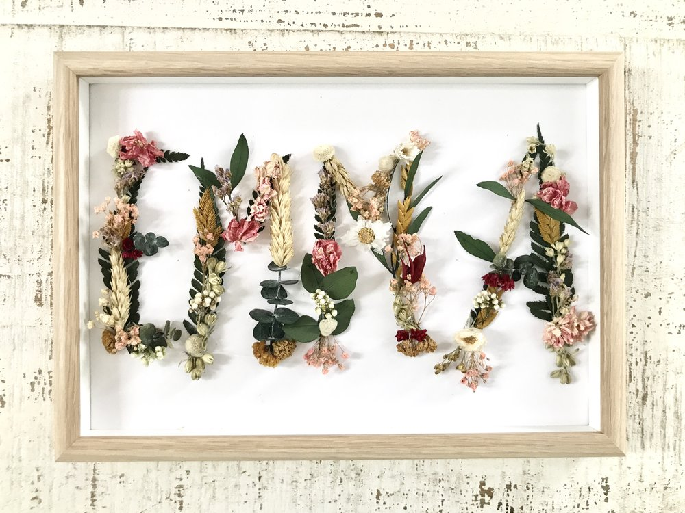 Iniciales enmarcadas de flores secas y preservadas