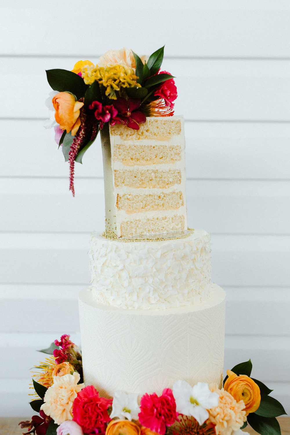 How to Nail a Tropical Wedding Theme - THE BRIDES TREEThe cake featured in this zesty and fun shoot by Milk and Honey Cake Creative was a deliciously on-theme tiered passionfruit and coconut cake. The top tier was covered in gorgeous gold, the mid layer in a coconut flake ruffle hand-painted with a gold trim and the base layer stamped with a beautiful ornate pattern.