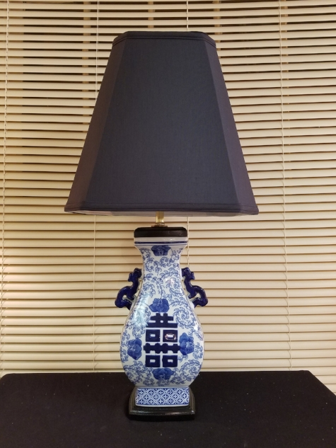"Rectangular Blue & White Porcelain Lamp    This lamp is made from a Blue & White Porcelain Vase. Designed with matching wood base and top cap, painted black. The vase is rectangle, so the lampshade is also made in a rectangular shape. Lamp stands 27"" tall to the top of the custom Black Silk lampshade.     $225.00, plus shipping"