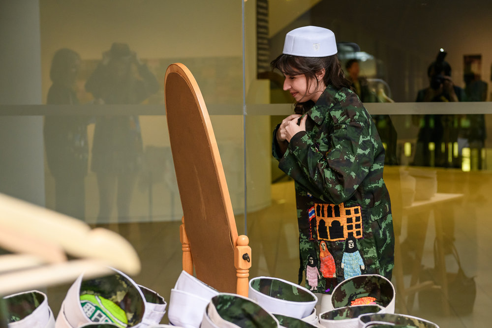A visitor interacting with the embroidered military jacket and kabiyoh in Jakkai Siributr's installation 'Changing Room', 2017. Image courtesy of Institute of Contemporary Arts Singapore, LASALLE College of the Arts (photo: Weizhong Deng).
