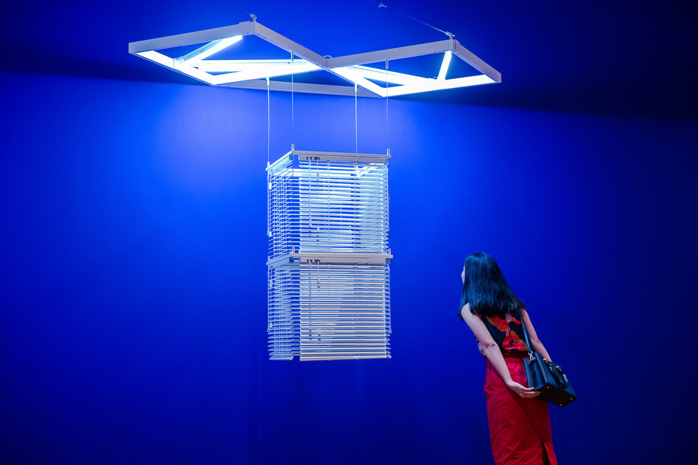 Haegue Yang, 'Sol LeWitt Upside Down – Double Modular Cube, Scaled Down 29 Times', 2017, aluminium venetian blinds, powder-coated aluminium hanging structure, steel wire rope, LED tubes and cable, 155 x 204 x 104 cm. Private collection, Taipei. © Haegue Yang, image courtesy of National Gallery Singapore.