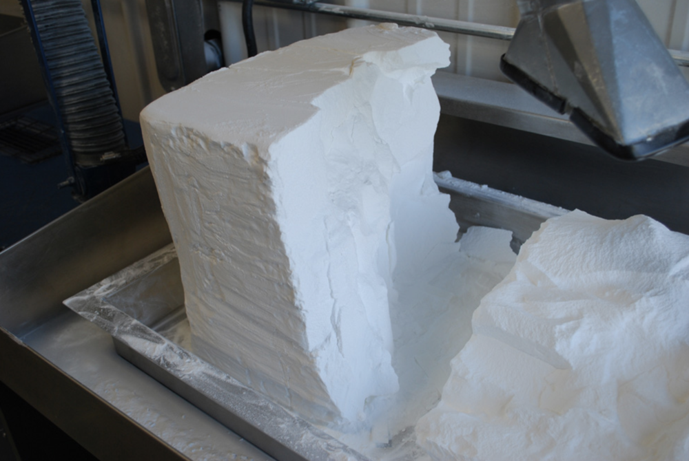 Slika prikazuje veliku količinu posebnog praha za SLS. Unutar prikazane hrpe praha krije se već gotovi model.