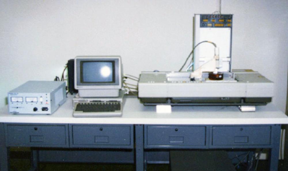 """Stereolitography apparatus, izvor: sculpteo.com  Hullov uređaj bio je prva verzija SLA 3D pisača.  Sigurni smo da bi većina ljudi smatralo FFF tehnologiju 3D ispisa prvom ikada, jer je podosta jednostavna, jednostavno se ponavlja proces """"sloj po sloj"""" plastike do konačnog objekta. No to nije istina. Prva i najstarija tehnologija 3D ispisa je ipak SLA, a mi ćemo pokušati opisati i objasniti tu tehnologiju.  Ono što ćete prvo uočiti uspoređujući FFF i SLA je cijena. SLA uređaji su u pravilu skuplji od FFF uređaja upravo zbog same kompleksnosti tehnologije. Zbog toga danas ne postoje SLA 3D pisači od nekoliko tisuća kuna (mislimo na cijenovni rang 3.000-7.000kn), dok FFF uređaje možete pronaći po tim cijenama.  SLA je tehnologija kojom se polimerizira viskozna tekućina koja podsjeća na smolu koristeći se laserom u čvrsti i funkcionalni objekt (model).  SLA uređaji koriste tzv. galvanometre (najčešće se nalazi jedan na x osi i jedan na y osi) koji služe za usmjeravanje svjetlosti (najčesšće laserske zrake) kroz posudu u kojoj se nalazi viskozna tekućina koja se polimerizira u željeni oblik. Softver kojim korisnik upravlja SLA uređajem šalje niz koordinata galvanometrima kako bi se laserska zraka usmjerila na točne lokacije na kojima se vrši polimerizacija tekućine. Isto kao i kod FFF tehnologije 3D ispisa, 3D model kojeg korisnik planira ispisati na SLA uređaju se """"razbija"""" na slojeve, odnosno ogromnu količinu koordinata za galavnometre koji usmjeruju lasersku zraku koristeći dobivene koordinate; prema dnu posude u kojoj se nalazi viskozna tekućina koju laserska zraka polimerizira na određenim mjestima, i tako se sve ponavlja do kraja ispisa."""