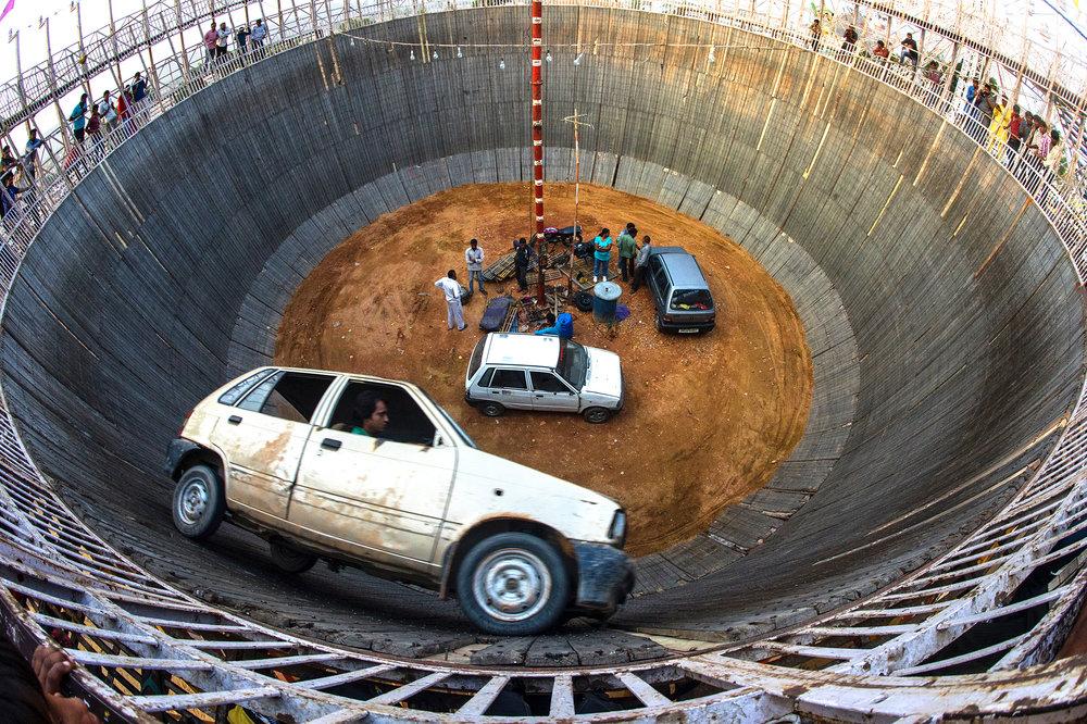 """L es coureurs de la """"Maut Kakuan"""" se préparent à stupéfier le public avec leurs cascades défiant la mort. Le Well of Death est l'arène où ils se produiront. Une fosse cylindrique et profonde faite de bois de cagette mesurant environ 15 mètres de diamètre et 20 mètres de hauteur. Ils rouleront sur ces murs verticaux, avec des voitures et des motos à grande vitesse et sans aucun mécanisme de sécurité. Inspiré de la Board Track Racing, très populaire aux Etats-Unis, la """"Maut Kakuan"""" est arrivée en Inde il y a 40 ans où elle est devenue une attraction dans la plupart des foires à travers les villages Indiens. Les conducteurs roulent à la verticale du sol. Ils montent en flèche au sommet de la fosse. En passant, ils saisissent les billets offerts par les spectateurs. Les cavaliers sont en """"suspension"""" pendant presque 12 minutes. Ils commencent leur descente dans un jeu mutuel dangereux de cercles diminuants jusqu'à ce qu'ils touchent terre de nouveau. Les héros s'inclinent et saluent la foule.   T he riders of the """"Maut Kakuan"""" are preparing to amaze the public with their stunts defying death. The Well of Death is the arena where they will perform. A cylindrical and deep pit made of crate wood measuring about 15 meters in diameter and 20 meters in height. They will drive on these vertical walls, with cars and motorcycles at high speed and without any safety mechanism. Inspired by the Board Track Racing, very popular in the United States, the """"Maut Kakuan"""" arrived in India 40 years ago where it became an attraction in most fairs across Indian villages. The drivers drive vertically on the ground. They soar to the top of the pit. By the way, they seize the tickets offered by the spectators. The riders are """"suspended"""" for almost 12 minutes. They begin their descent into a dangerous mutual game of diminishing circles until they touch down again. Heroes bow and greet the crowd."""