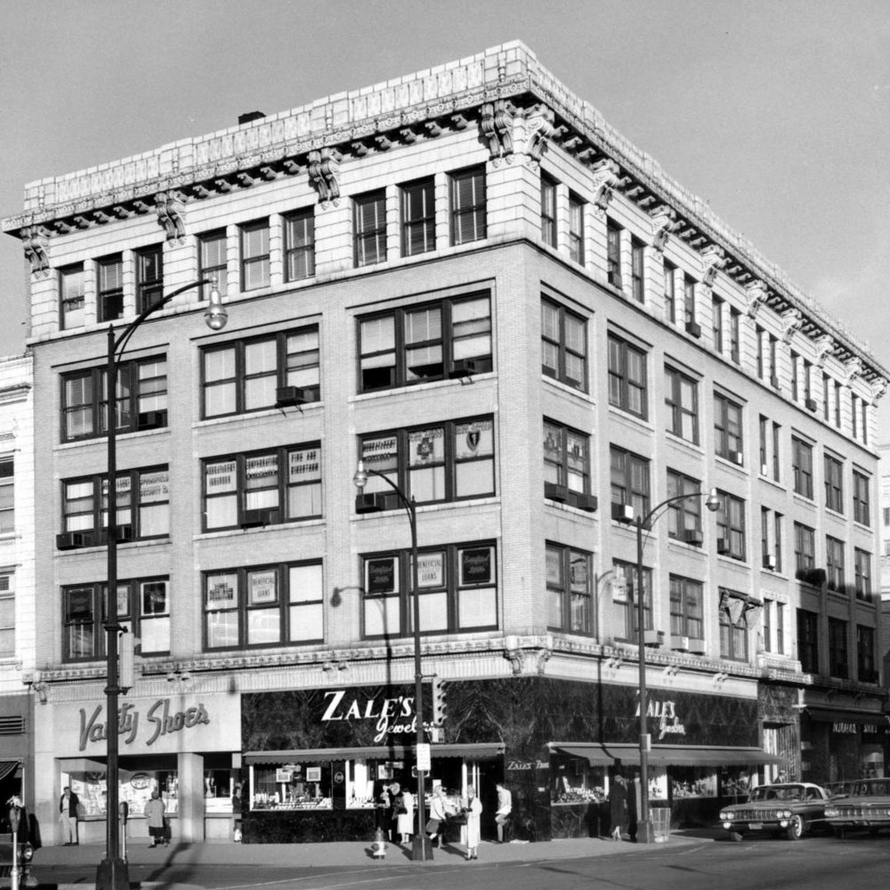 c. 1950s - The Holland mid-century. Zales Jewelry and Vanity Shoes are staples on the square.