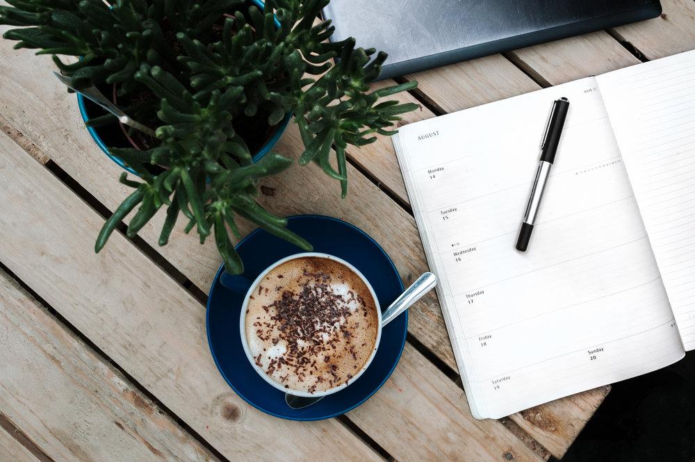 Calendar book, coffee & a plant