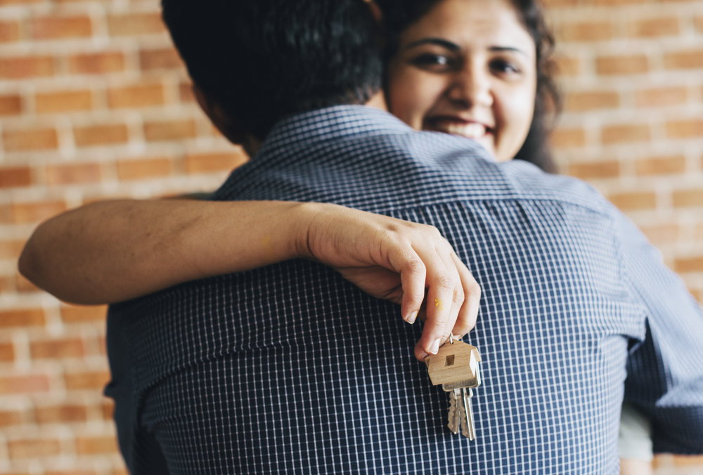 People hugging after receiving the keys to their new home because their mortgage closed on time.