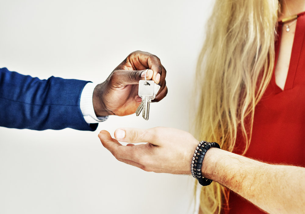 Man handing over house keys to a woman after she closes on her new house!