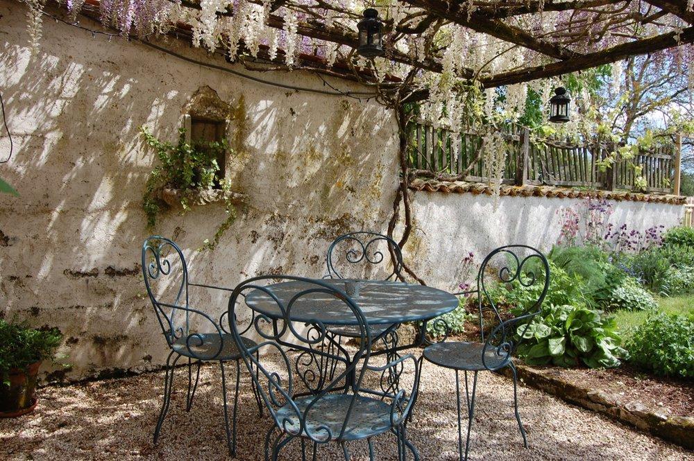 Springtime under the pergola in the private garden at LES ECURIES