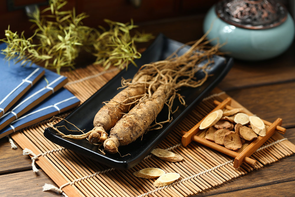 .ginseng in black plate on wooden table