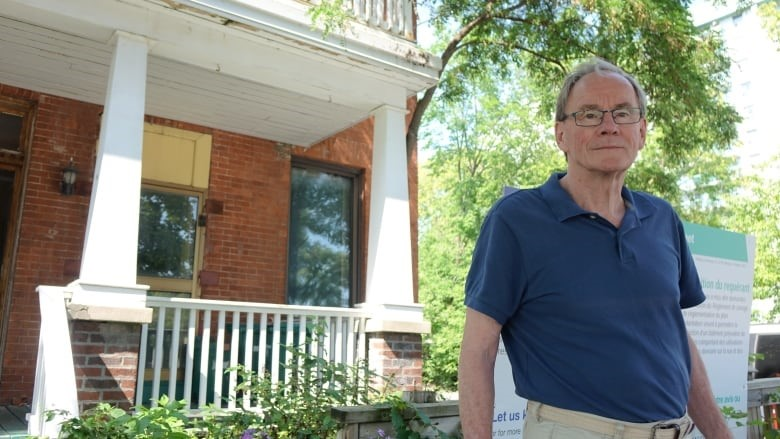Peter Ferguson, chair of the Lowertown Community Association's planning committee, praises Gaetan Chenier for preserving elements of the old house at the corner of Rideau and CoBourg streets. (Laurie Fagan/CBC)