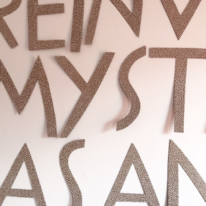 Letters cutout of cardboard cover with small white pen dots.