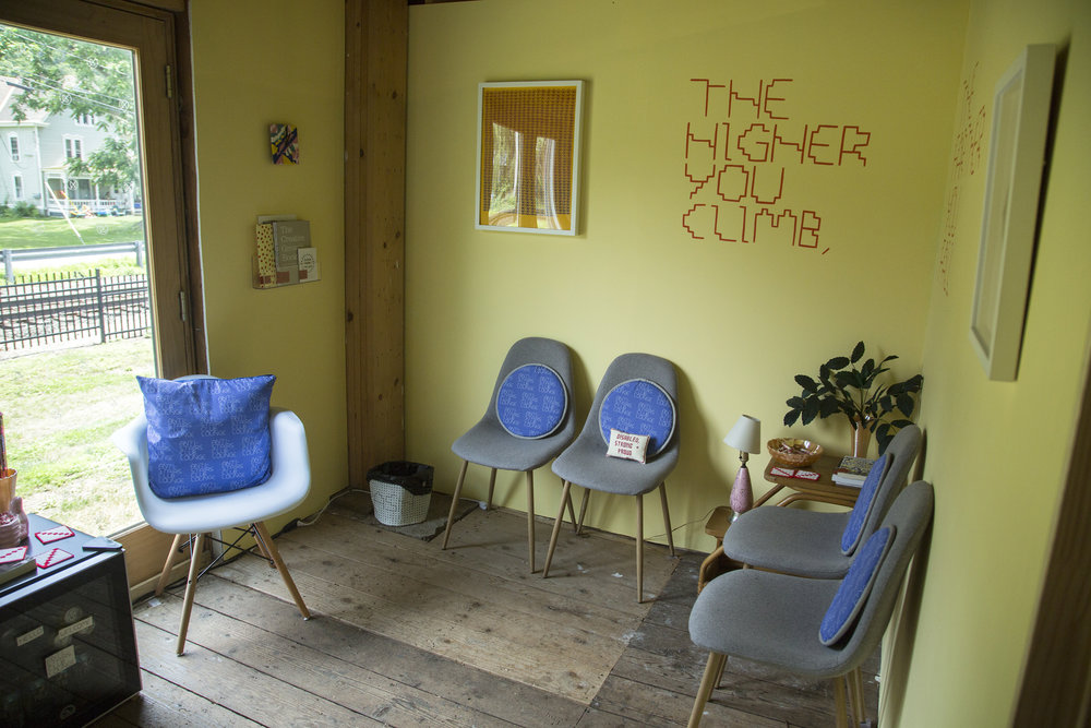 The interior of the lounge featuring chairs, reading materials, lamps, candy, and a mini-fridge.