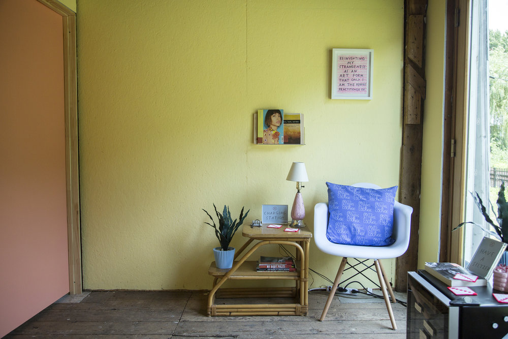 A corner of the lounge with a chair, a charging station, books, magazines, and a fake plant.