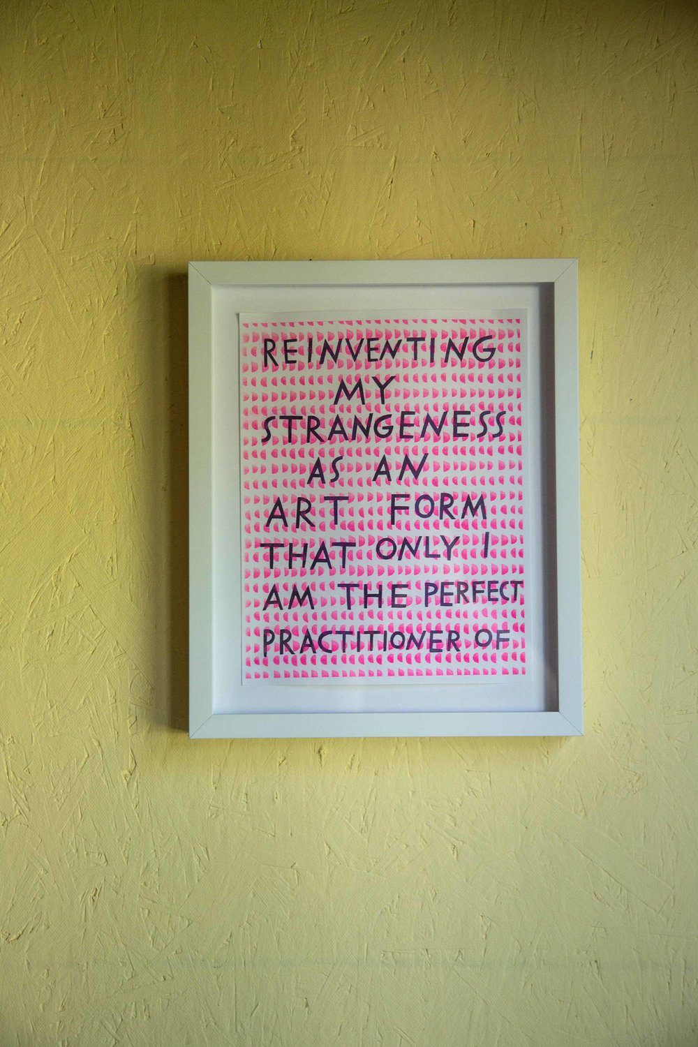 """A framed print reading, """"Reinventing my strangeness as an art form that only I am the perfect practitioner of."""""""