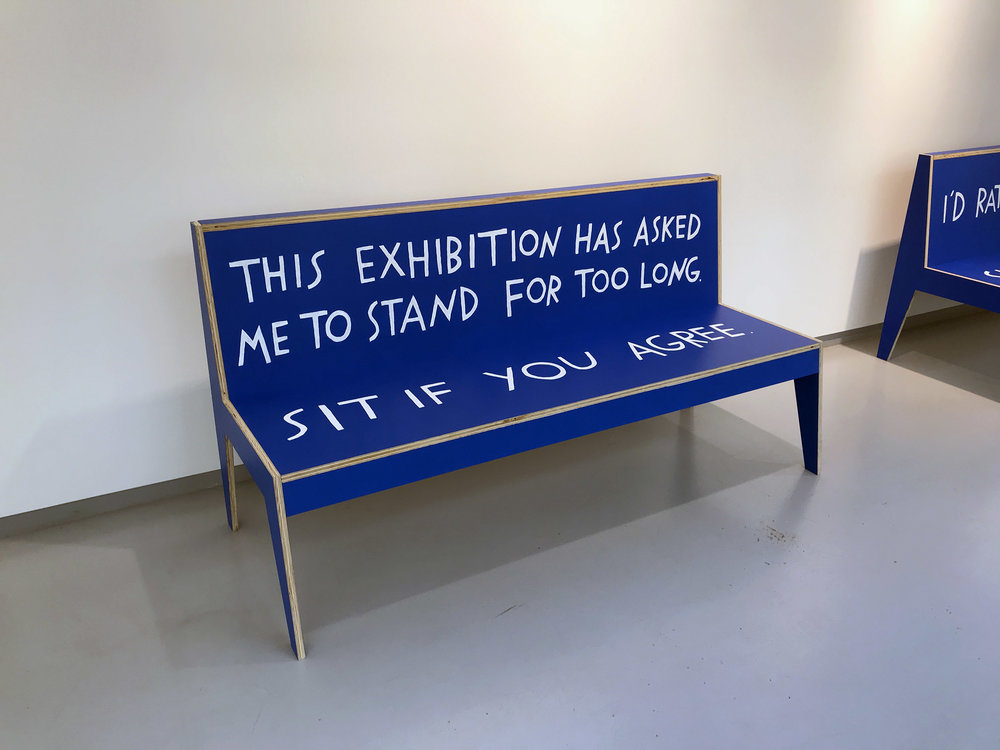 "A blue bench with hand-painted text that reads, ""This exhibition has asked me to stand for too long. Sit if you agree."""