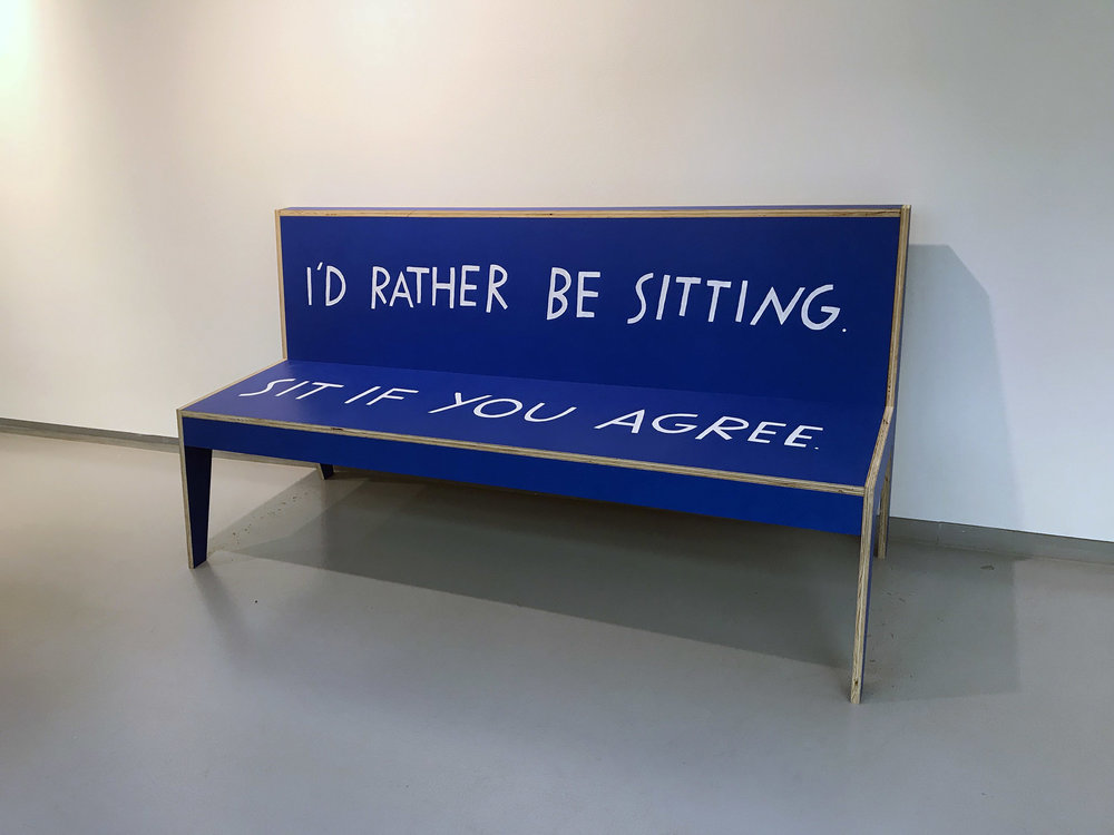 "A blue bench that reads, ""I'd rather be sitting. Sit if you agree."""