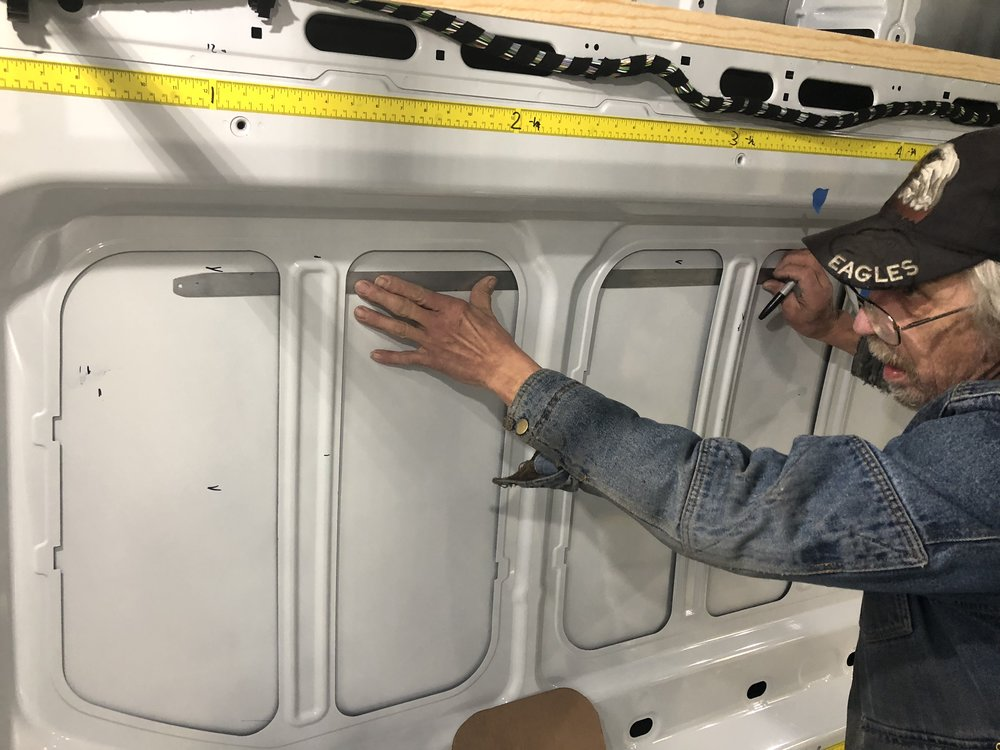 This is the window behind the driver's side. It's placed as far forward as possible. The top, left, right, and bottom edges have been measured and marked. Now George is connecting the lines.