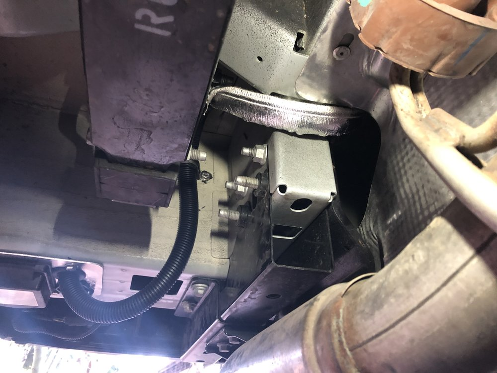 Over spare tire, and then over exhaust