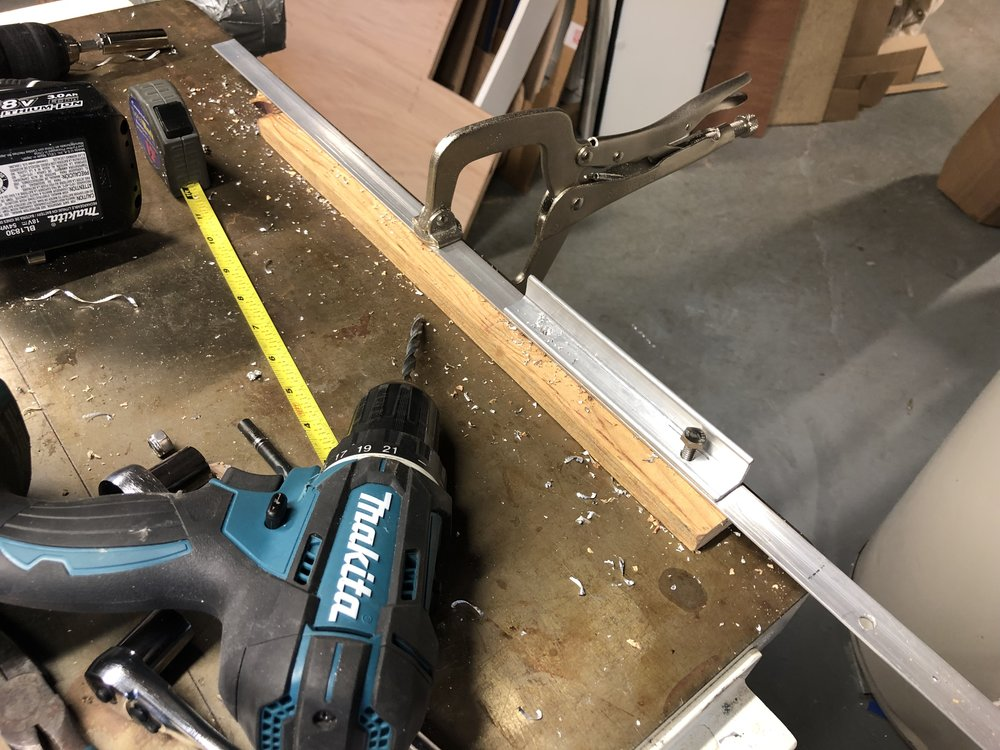 Using a short piece of angle as a drill jig for four-inch spaced holes.