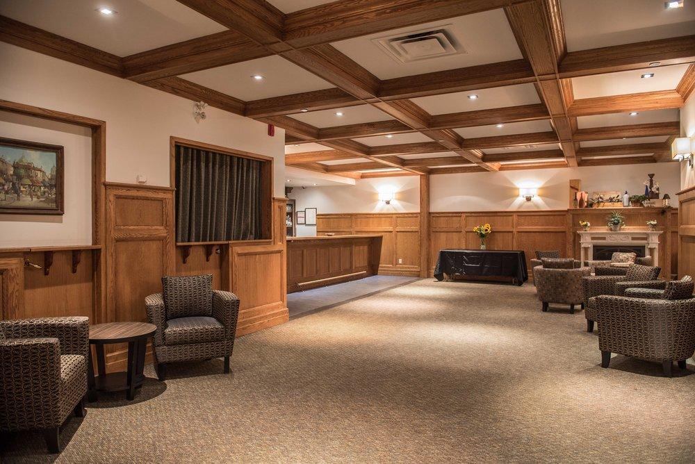 LE LOBBY - De 1300 pieds carrés, ce lobby est muni d'un service de bar complet, fabriqué de chêne. Près des tables, se situe une belle cheminée d'appoint, ornée de marbre blanc. Des meubles confortables sont installés autour de la cheminée et des vestiaires; les chaises, les fauteuils, et/ou tables sont disponibles selon vos dispositions et préférences personnelles pour vos demandes événementielles.Le lobby peut contenir jusqu'à 125 personnes (debouts) et peut être utilisé pour des petits rassemblements d'affaires, des kiosques, prestations musicales intimes, lancements, rencontres amicales et plus.