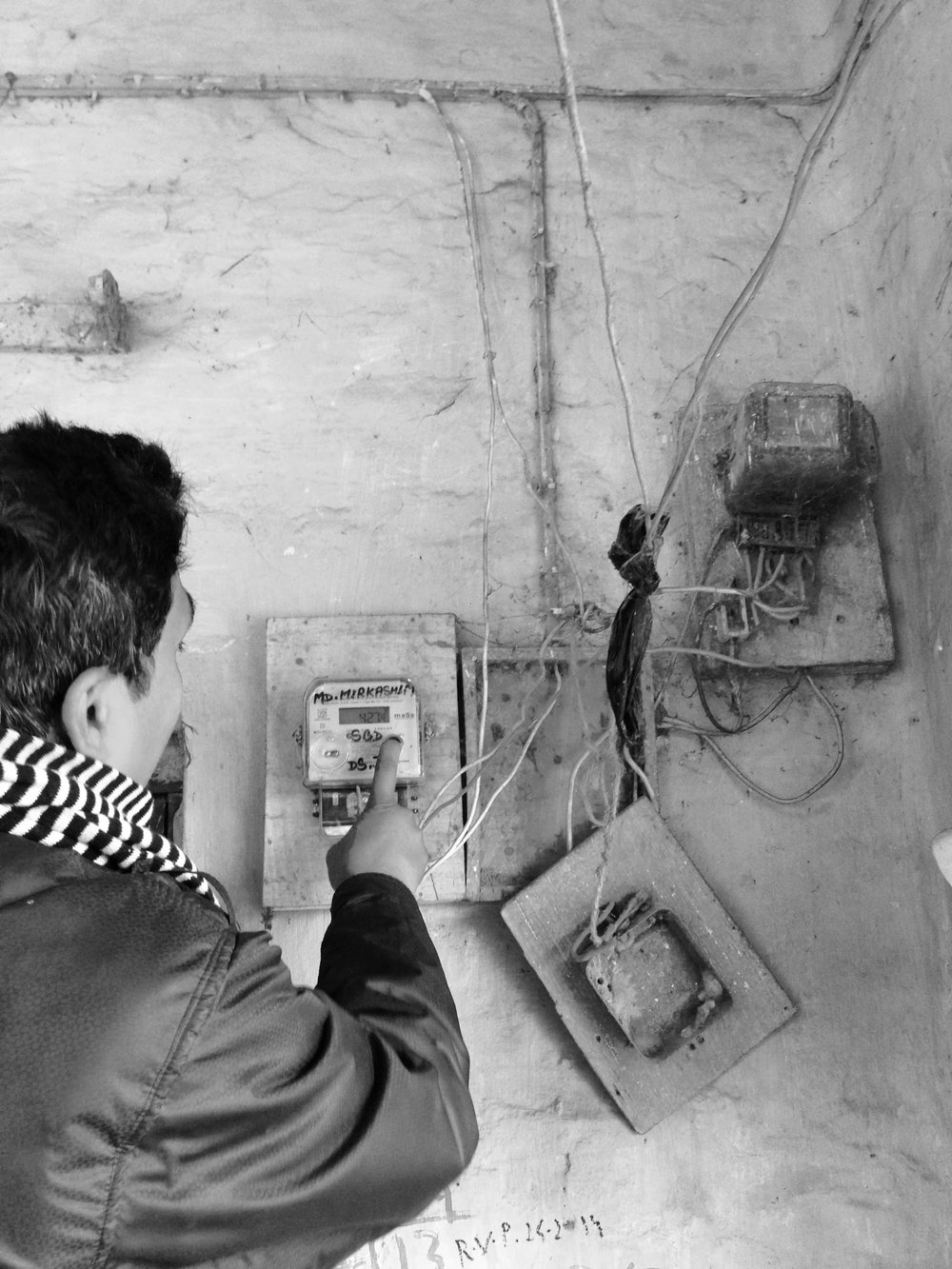 An employee of the Power Holding Company reads the electricity meter as part of his collection rounds across the state.