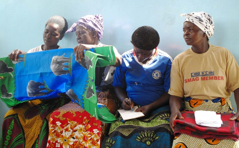 """Zambian mothers examine the contents in their """"mama kits""""."""