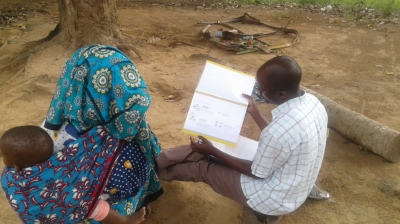 A community member in Kenya shares her preferences with IDinsight's Michael Otieno as he pilots a small probabilities visual aid.