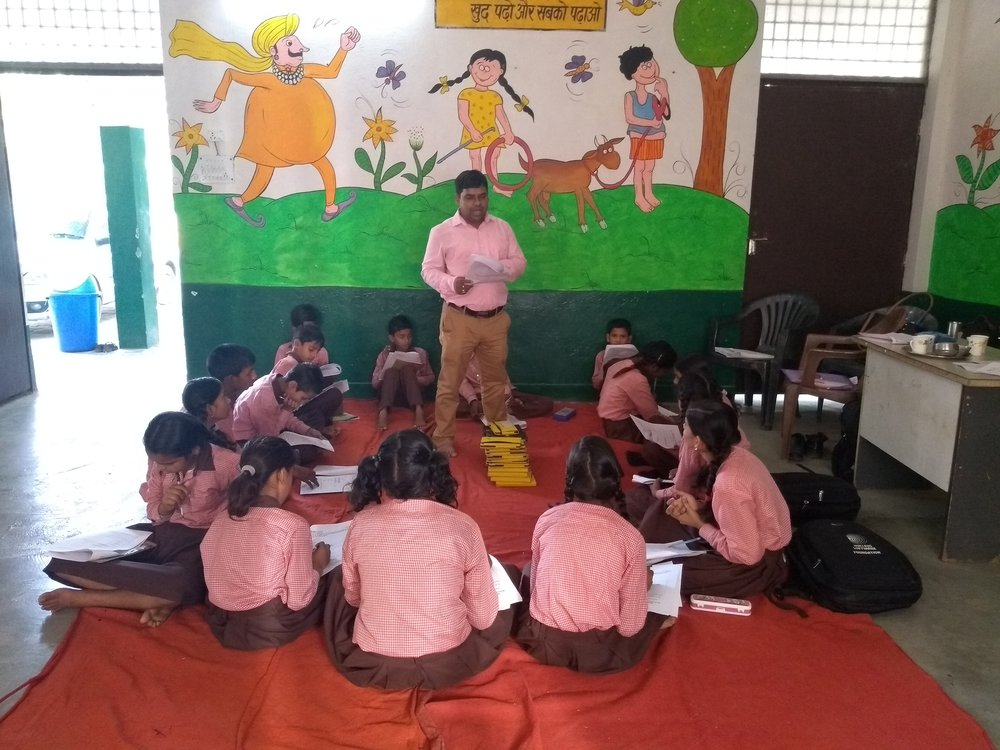 Students listen to instructions from IDinsight Senior Field Manager, Dinabandhu Bharti, on sharing their preferences on technology in the classroom.