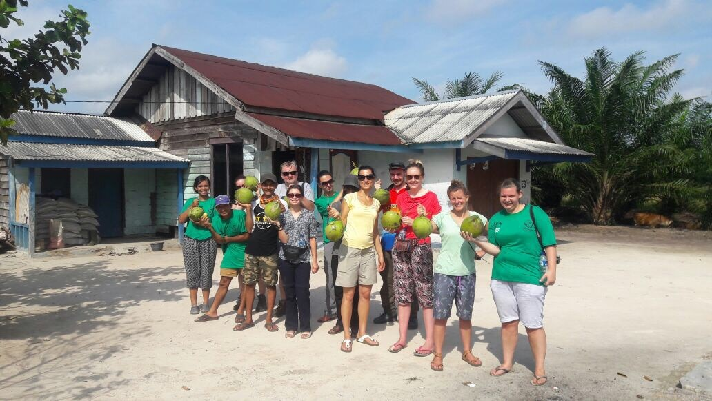 2016 Volunteers pose for a photograph, coconuts in hand.