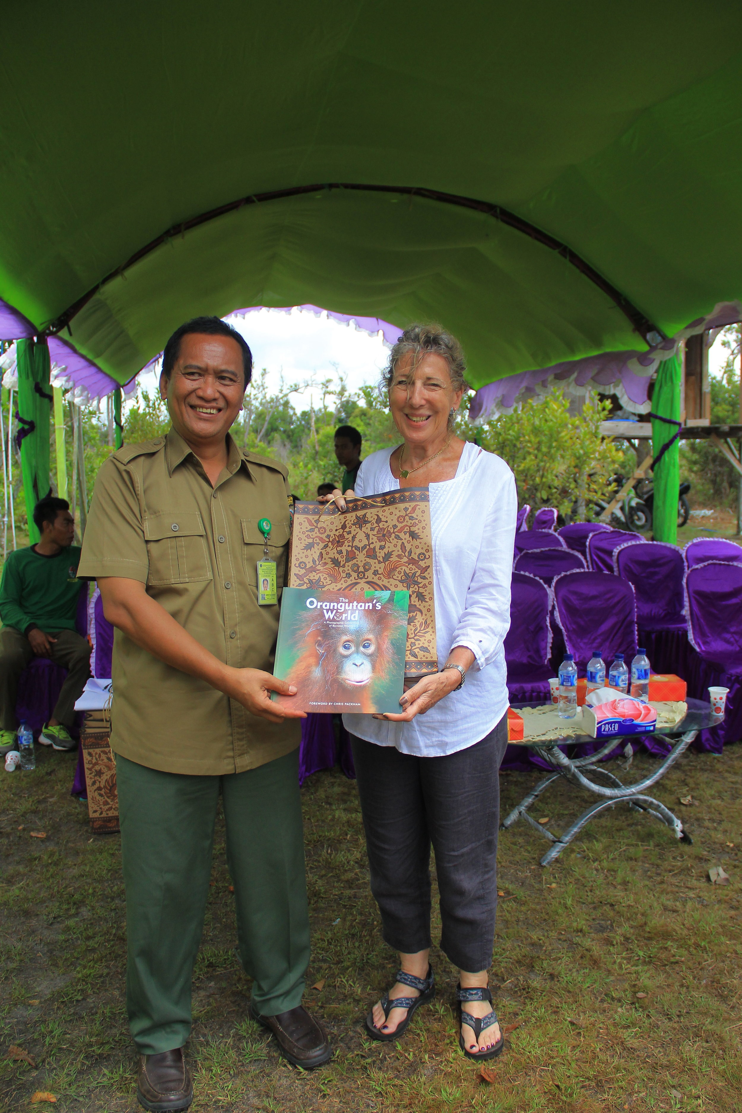 "OF Director Ashley Leiman OBE presenting a copy of our book ""The Orangutan's World"" to Pak Adib. Image© Orangutan Foundation."