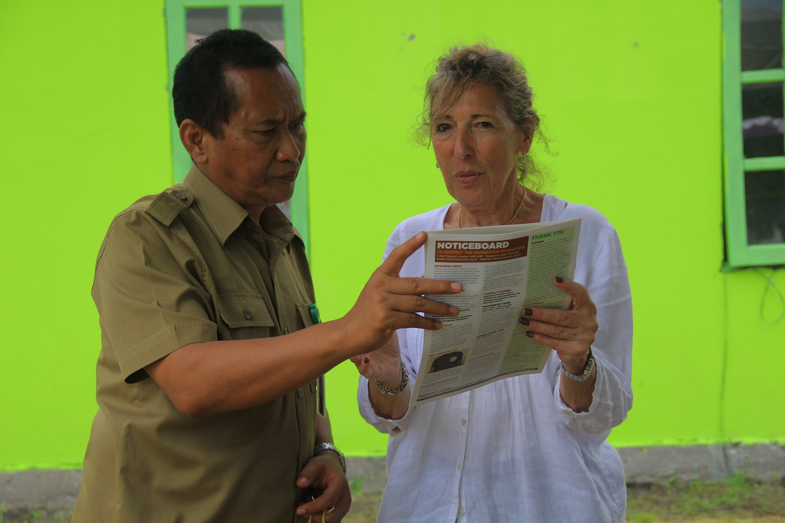 OF Director Ashley Leiman OBE and Pak Adib reading our latest issue of Red Ape. Image© Orangutan Foundation.