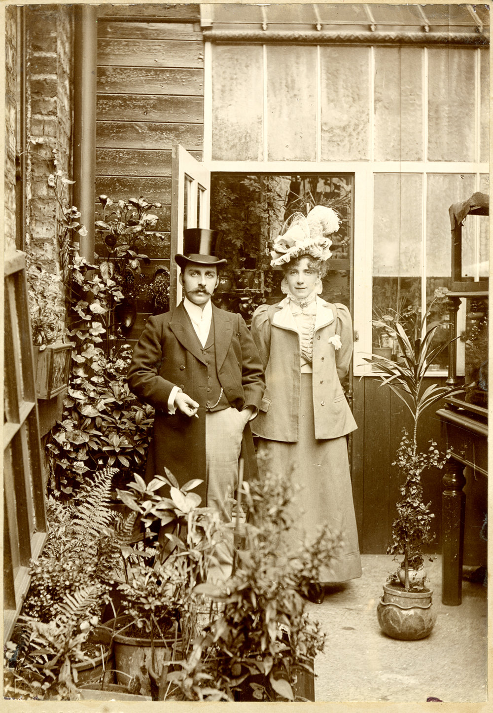 Surrounded by potted plants and climbing ivy, a well dressed couple pose by a green house door - about 1900